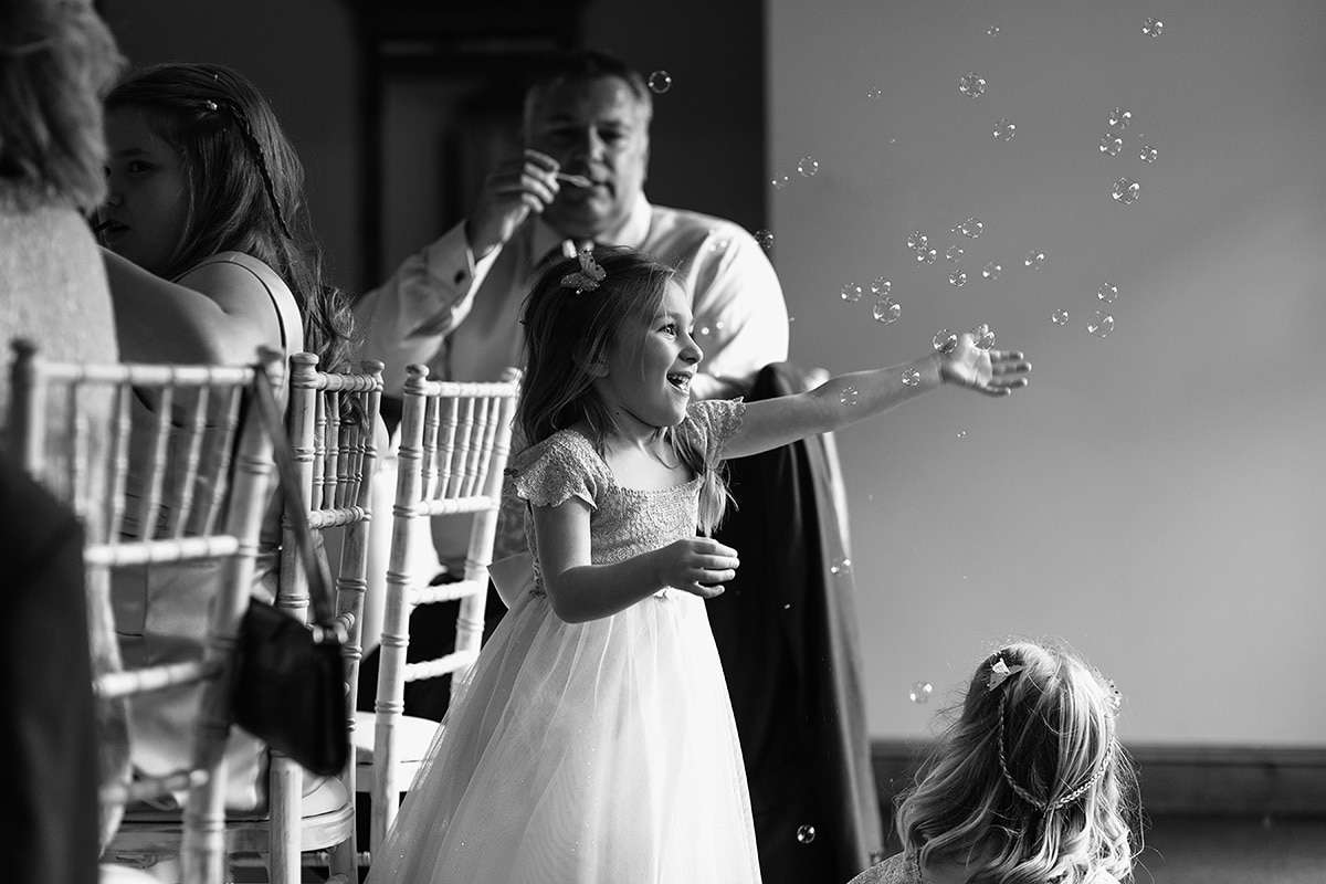 a flower girl catches bubbles