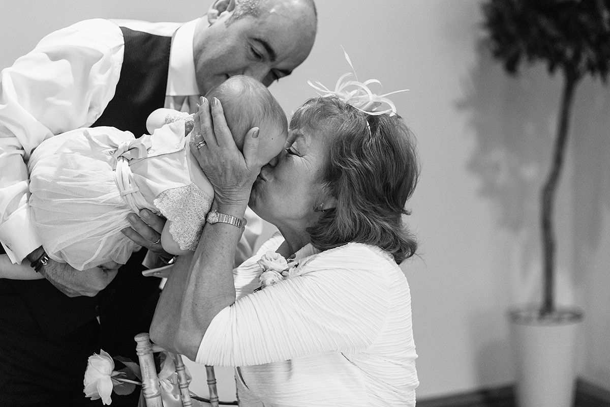 a guest kisses the couples new baby
