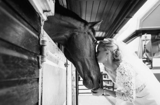 a bride with her horse on her wedding dat