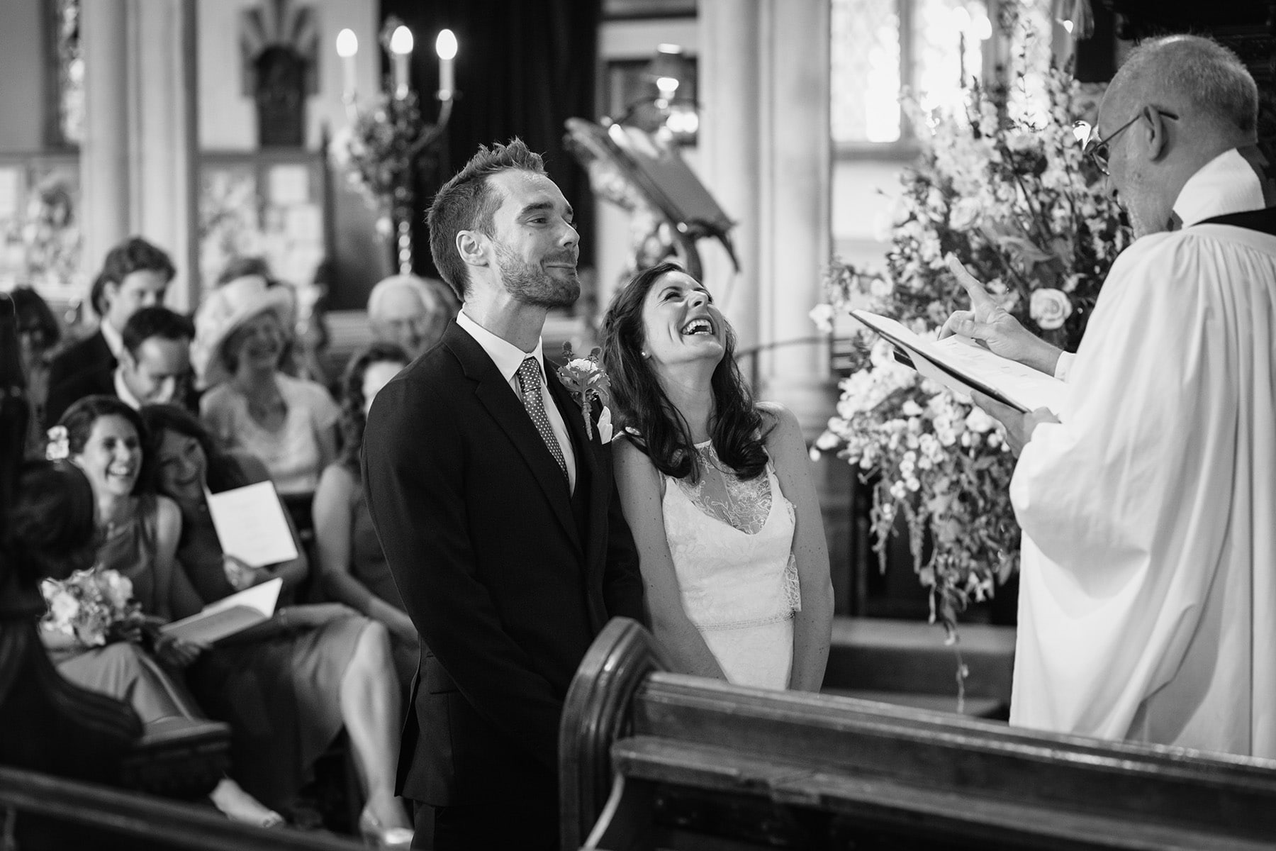 bride and groom laugh in southwold church