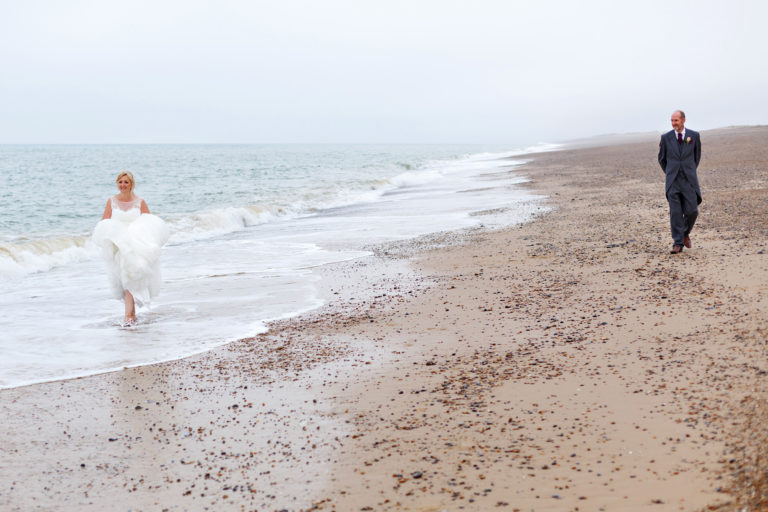 bride and groom on cley beach in north norfolk