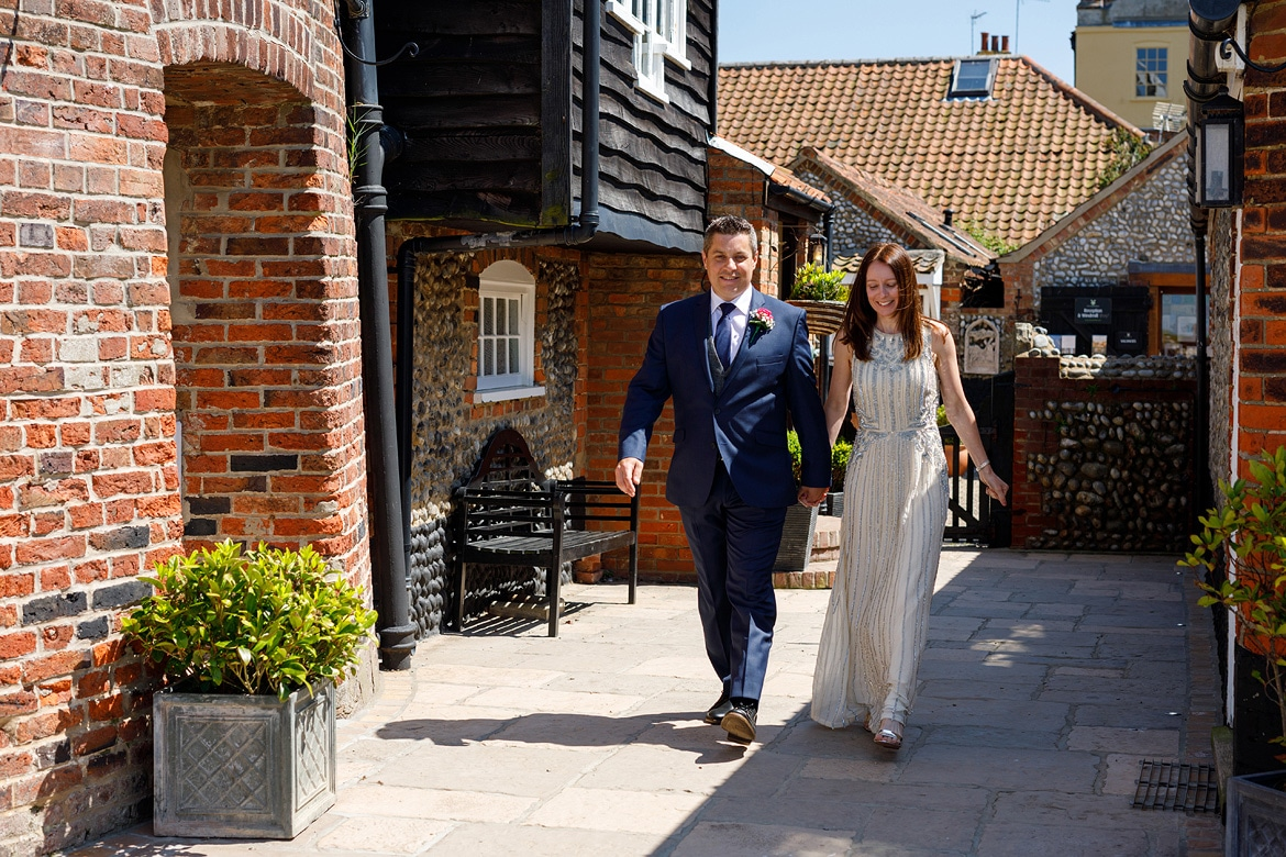 bride and groom walk in together to their cley mill wedding