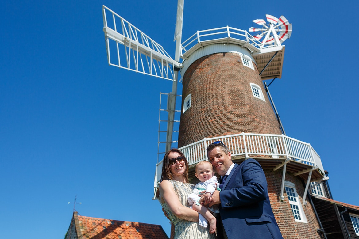 bride and groom with their baby in front of cley windmill