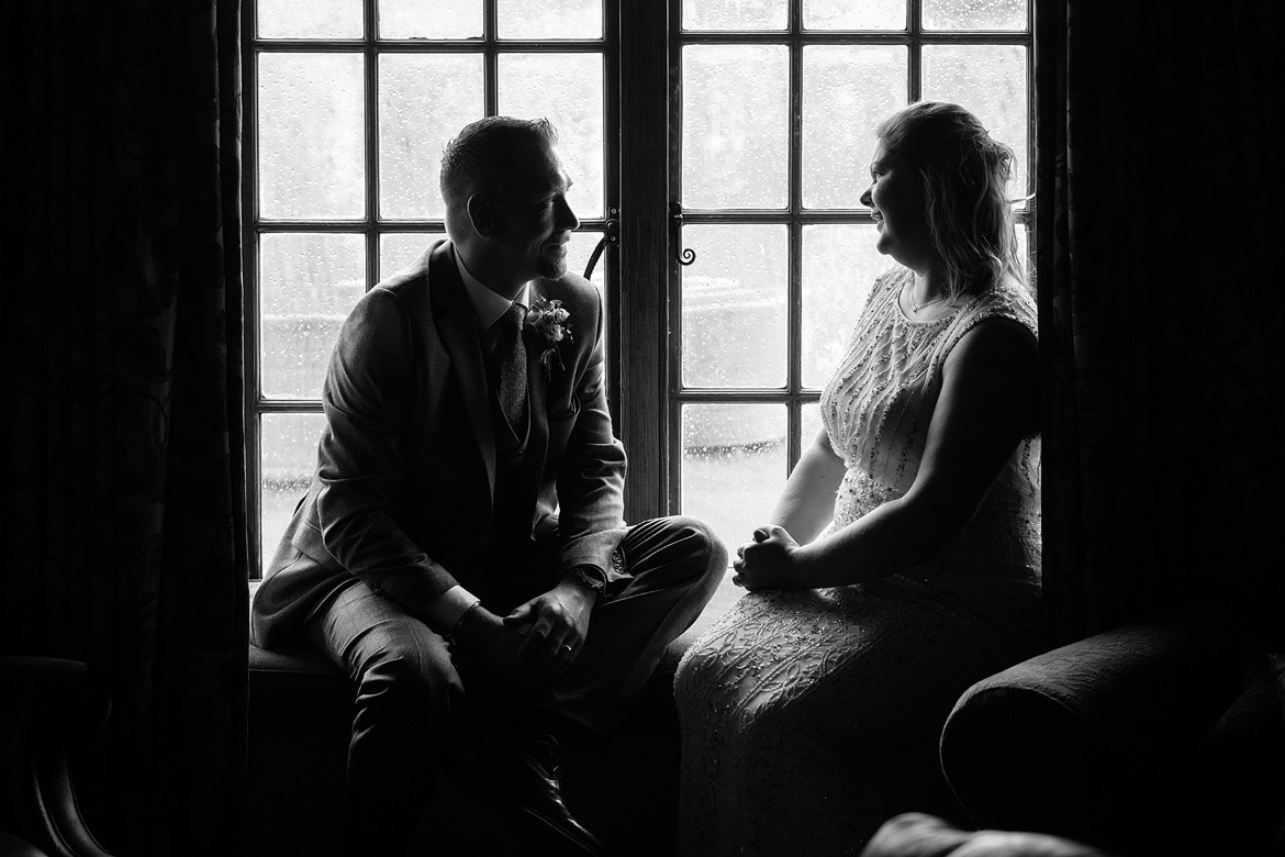 bride and groom in the window at their cley mill wedding