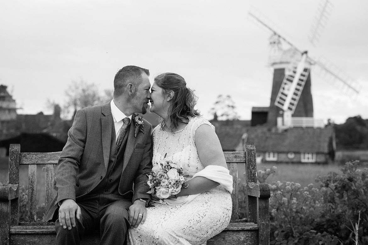 bride and groom on a bench with cley mill in the background