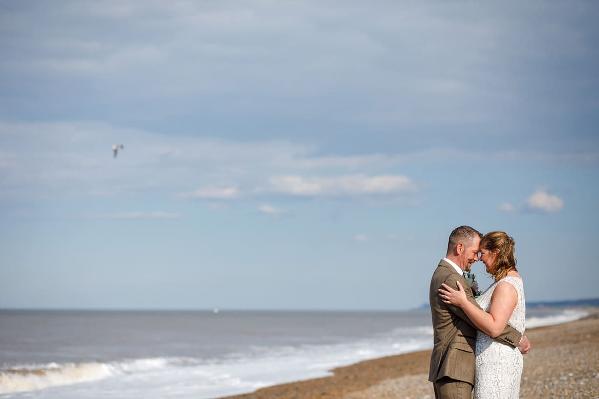 bride and groom on the beach after their cley mill wedding