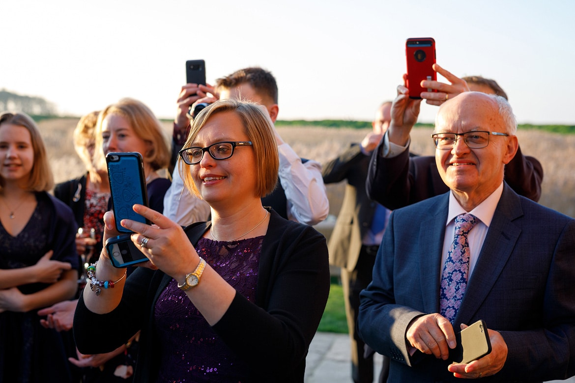 guests take photos of the couple