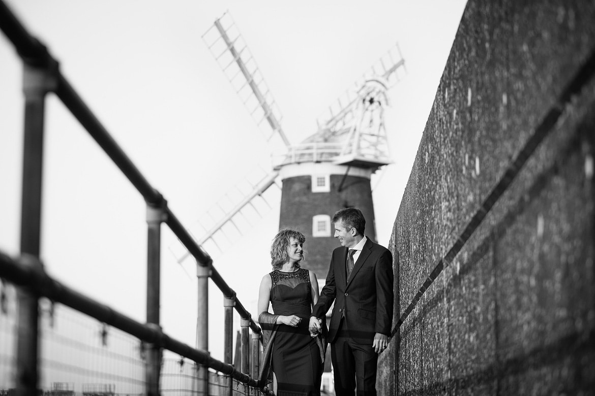 bride and groom walking at their cley windmill wedding