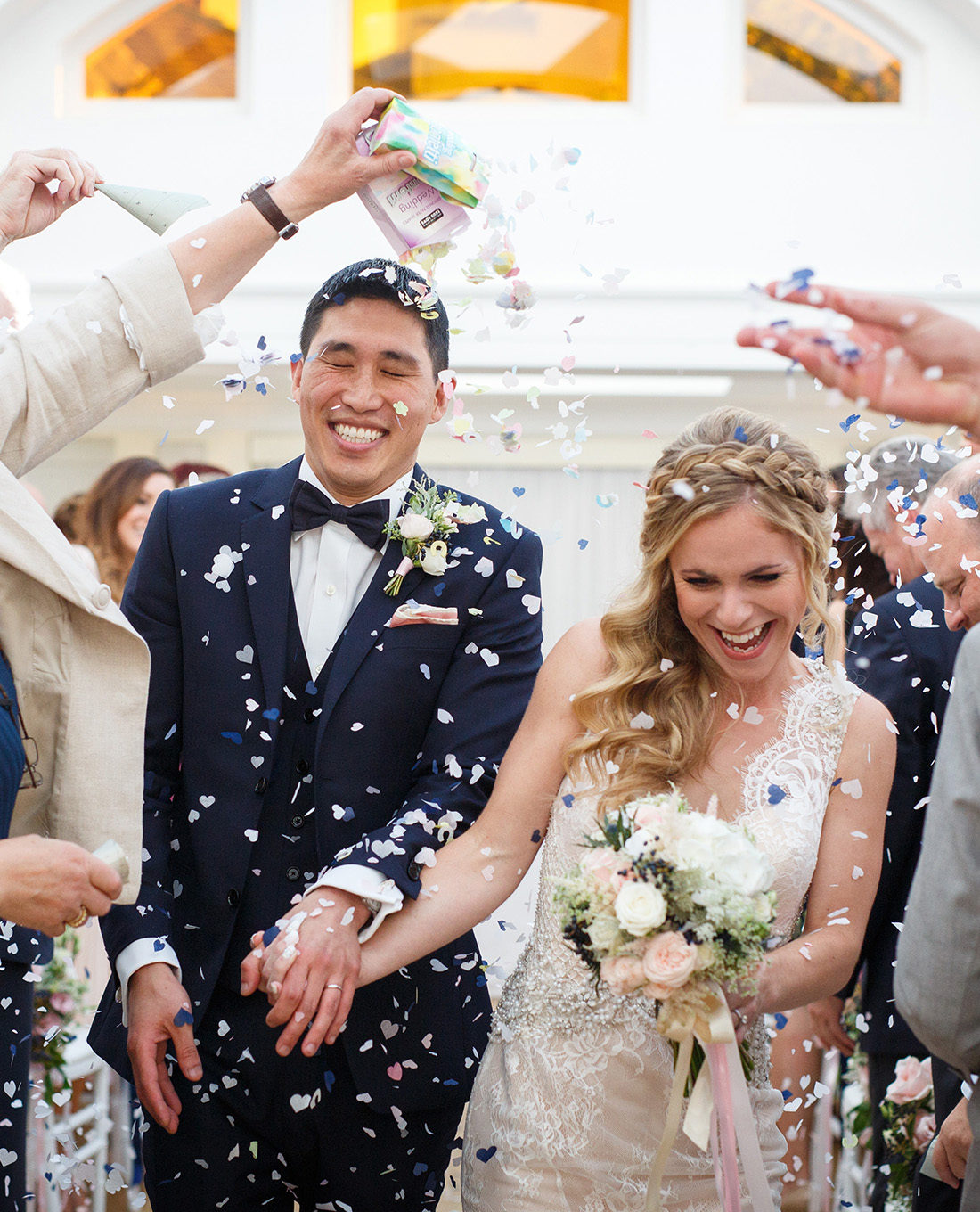 bride and groom running through confetti