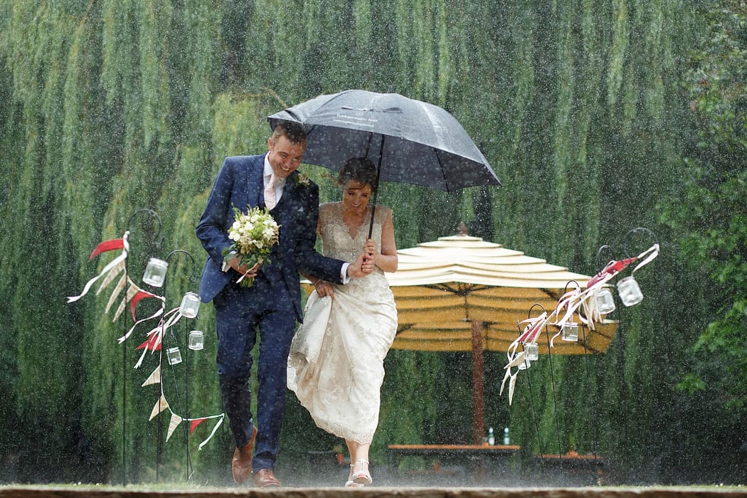 bride and groom running through the rain