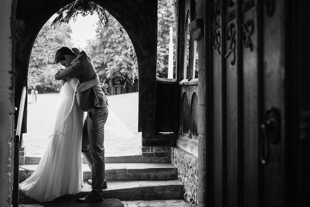 bride and groom in a church doorway
