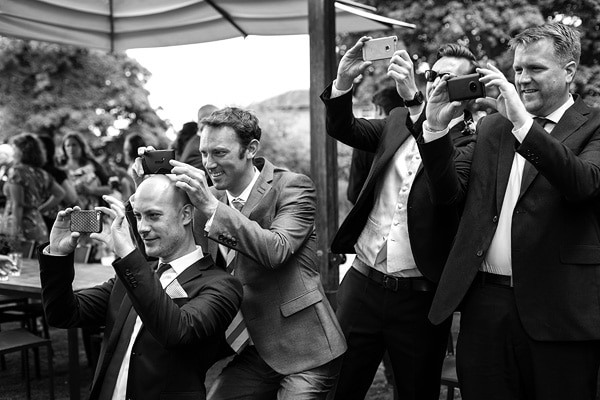 wedding guests taking photos on their mobile phones