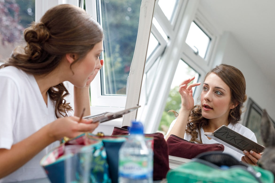 the bride applies her makeup in the mirror