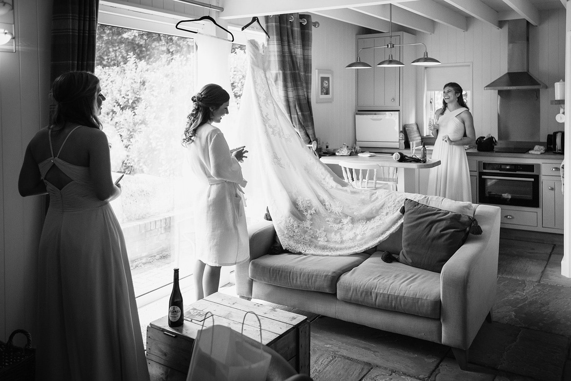 the bride takes down her dress from the window