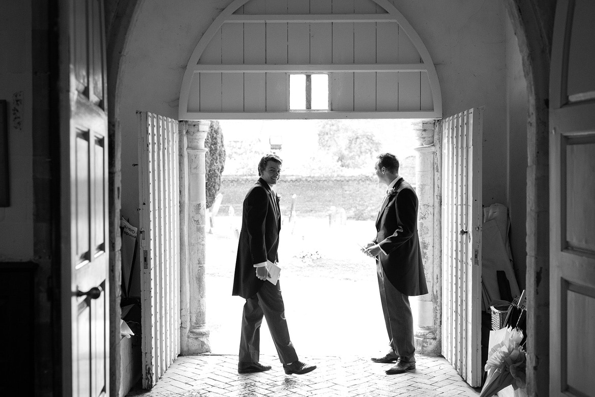 groomsmen shelter from the rain in the church porch