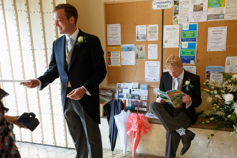 the groom reads a farming magazine in framlingham church