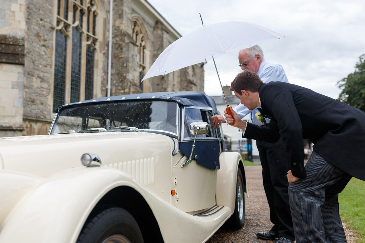 a groomsman offers his umbrella to the bride