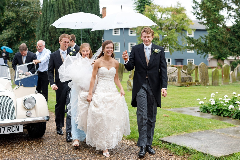 the bride walks through the rain into her framlingham wedding