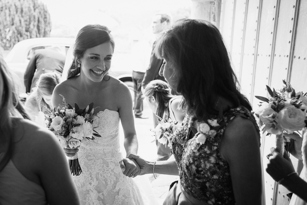 the bride is greeted by her mother in the church porch