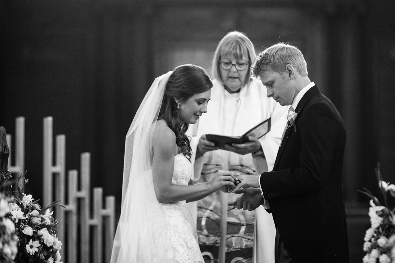 bride and groom exchange rings in framlingham church