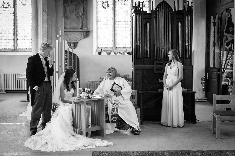 bride and groom sign the register in framlingham church