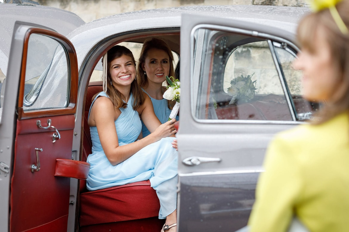 a bridesmaid waits to leave in the vintage wedding car