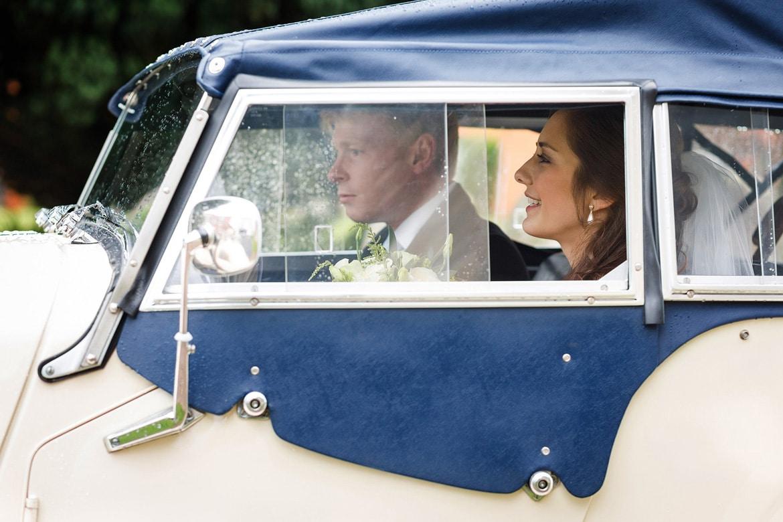 bride and groom in their vintage wedding car