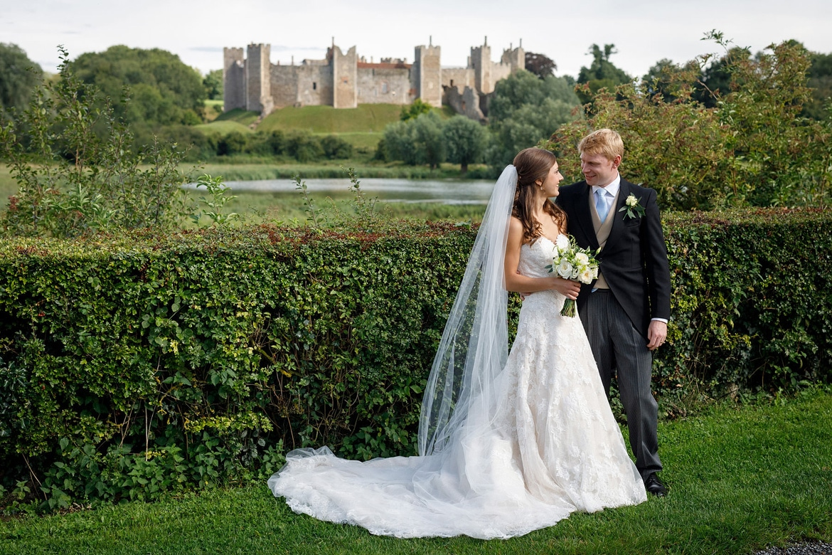 bride and groom pose with framlingham castle in the background