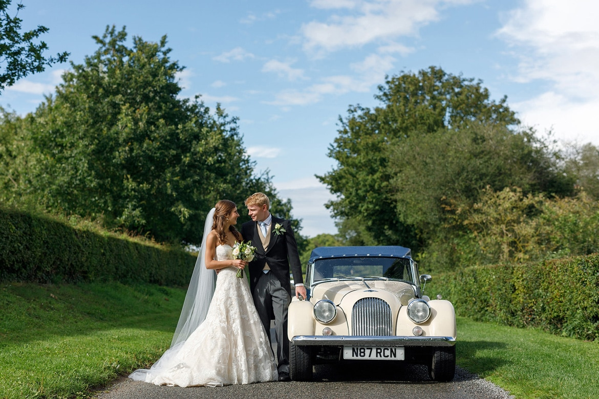 tom and anna pose with their vintage morgan wedding car