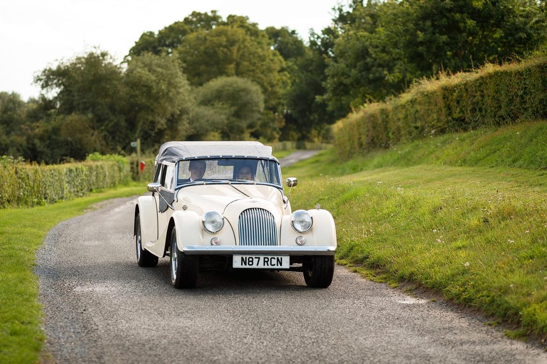 a vintage morgan drives along a lane behind framlingham castle