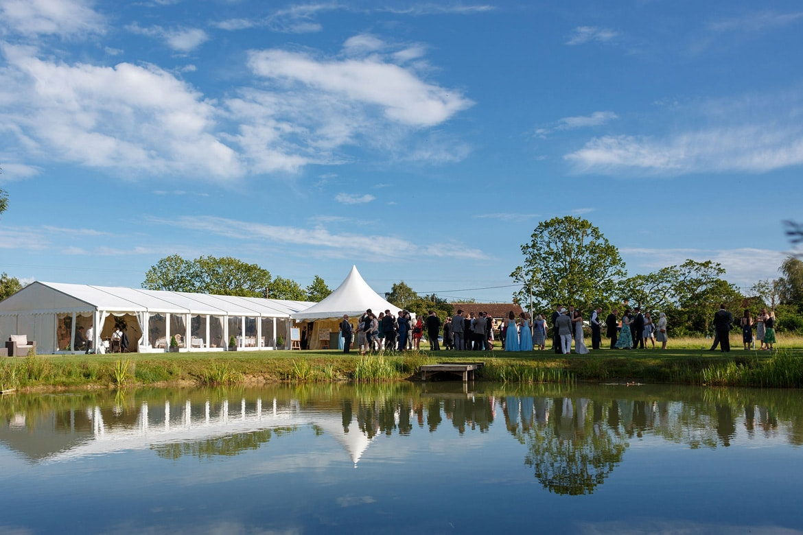 a marquee wedding in suffolk reflected in the pond