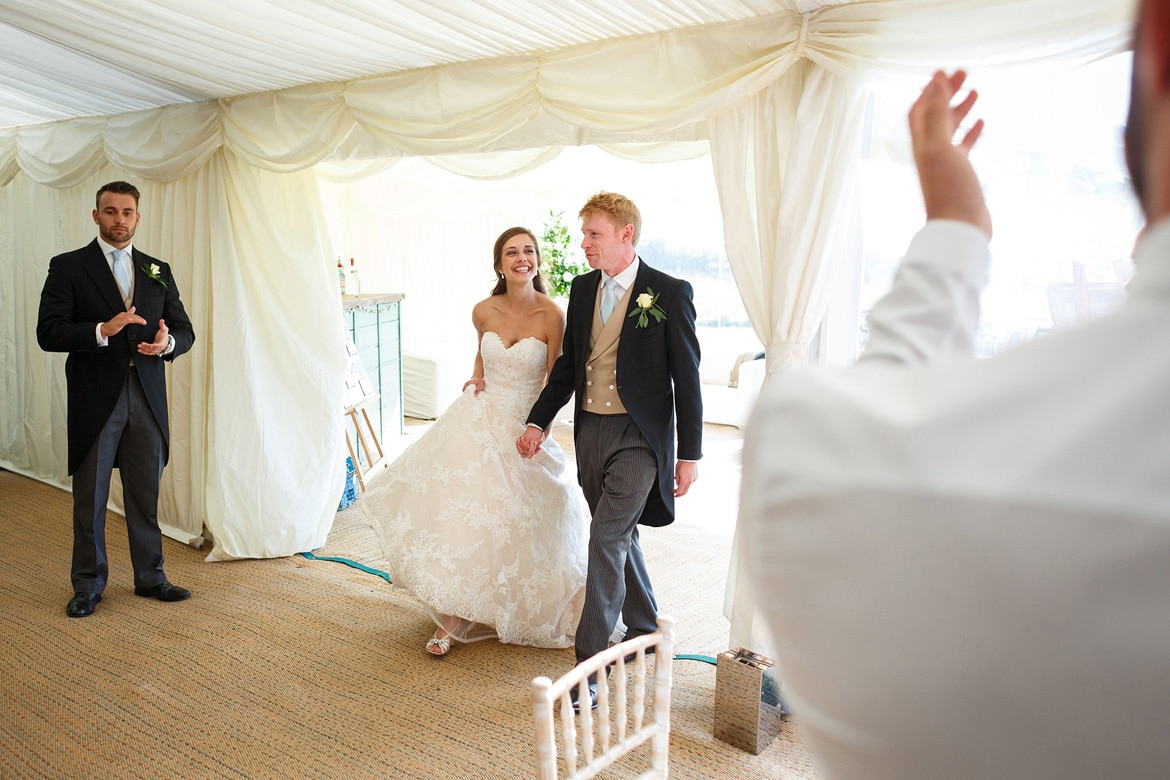 bride and groom walk into the marquee