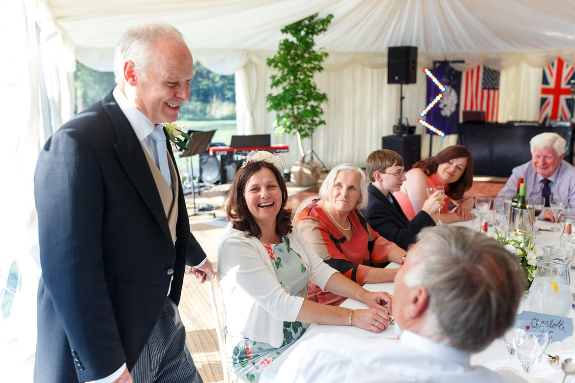 the grooms father laughs with the wedding guests