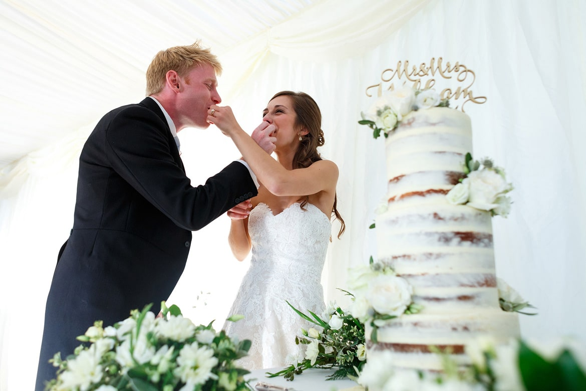 bride and groom exchange bites of their wedding cake