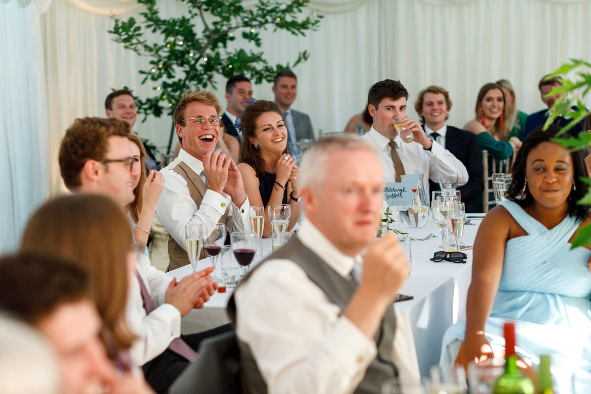 guests laugh at the grooms speech
