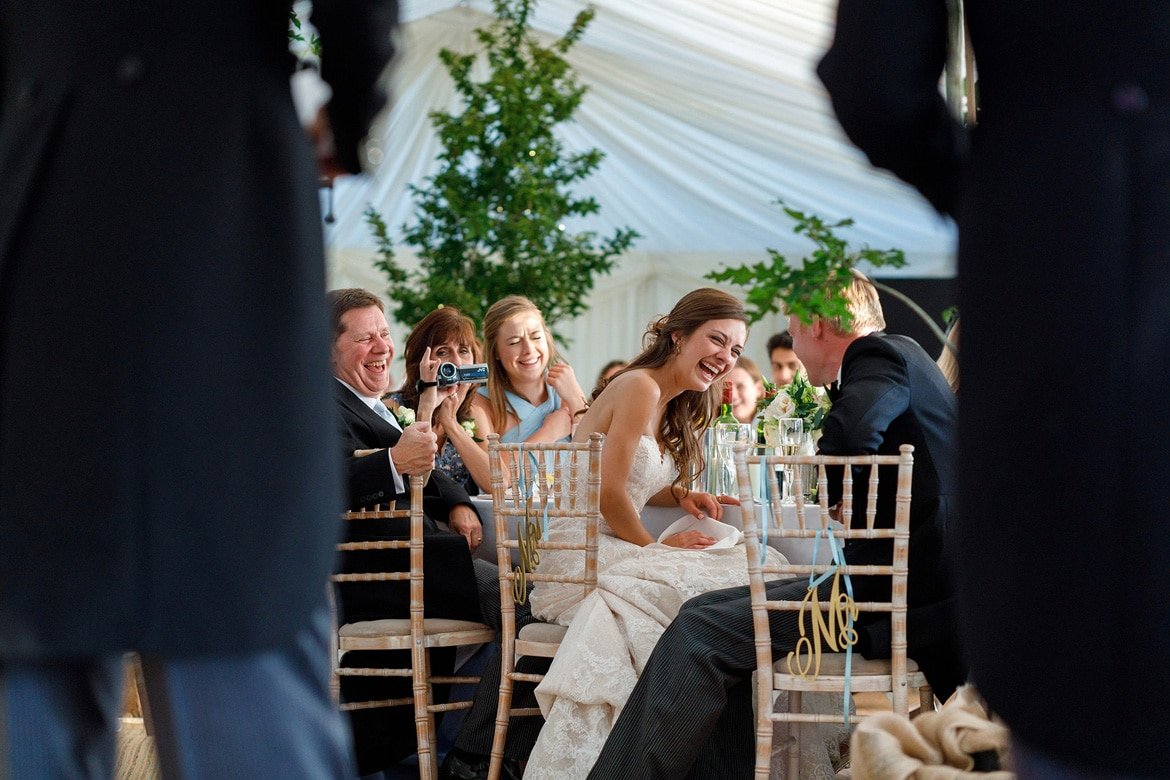 bride and groom laugh during the best mens speech