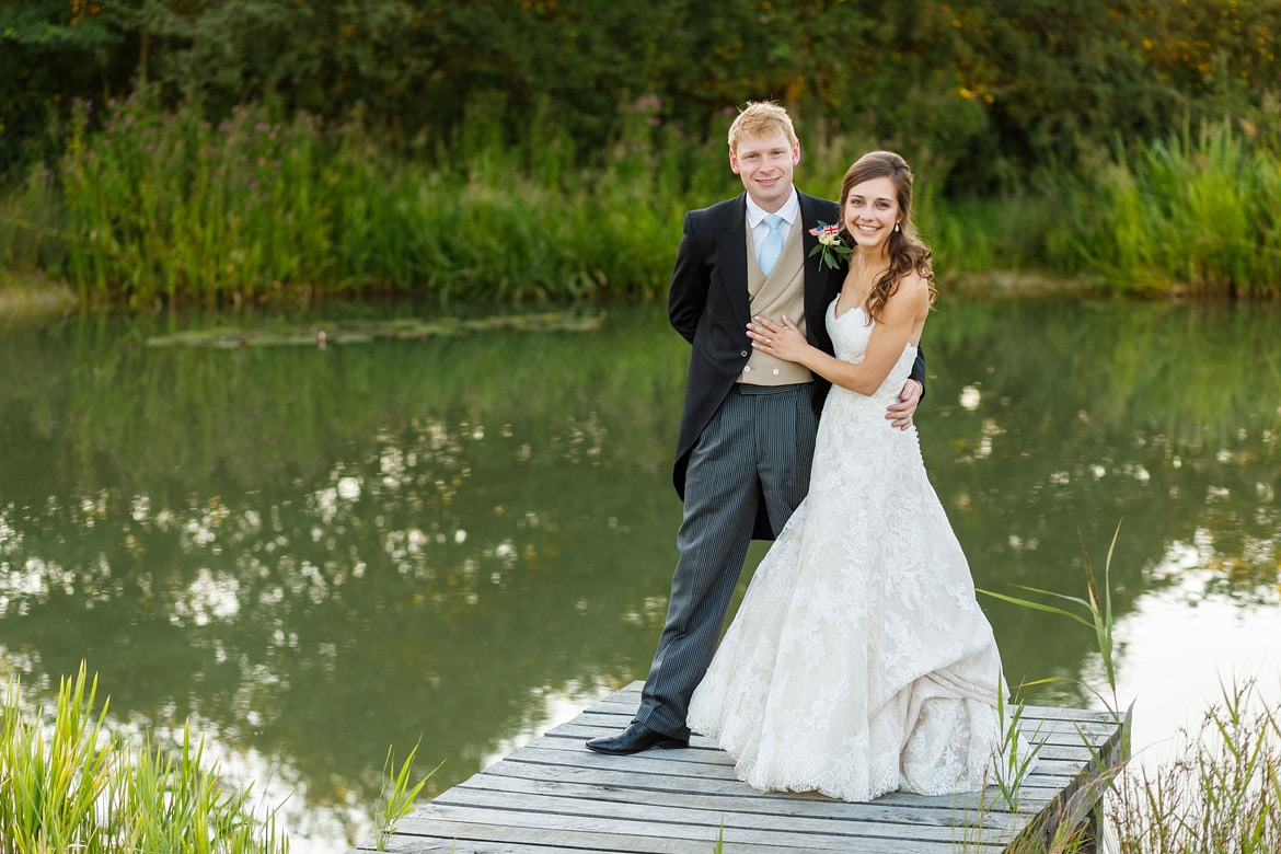 bride and groom pose on the jetty