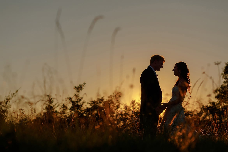 a bride a groom silhouette against a suffolk summer sunset