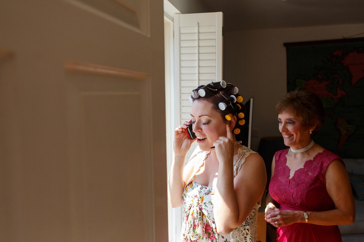 the bride speaks on the phone with her mother