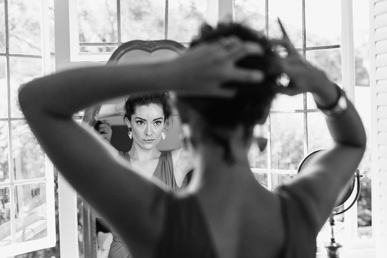 a bridesmaid fixes her hair