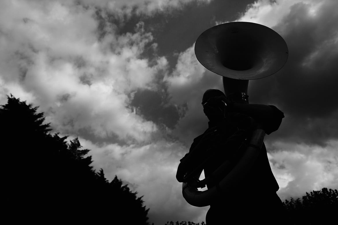a tuba player silhouetted