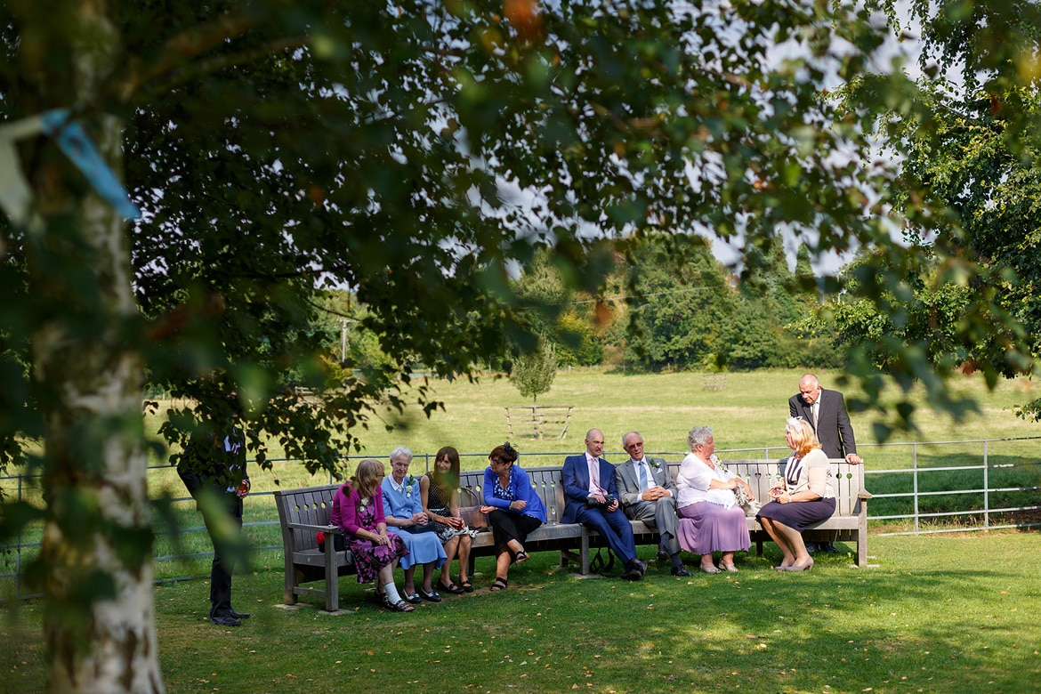 wedding guests seated in the shade of the trees