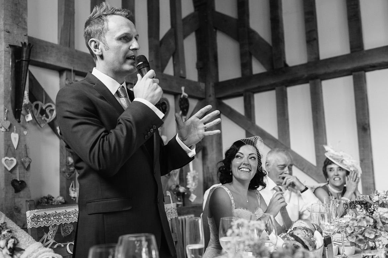 the groom speaks as the bride looks on