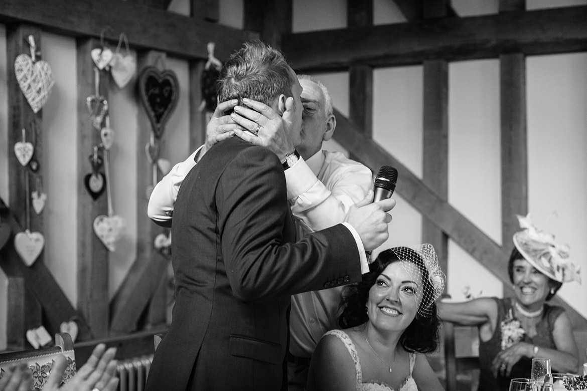 the father of the bride kisses the groom
