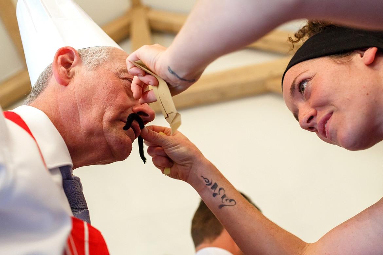 a waitress puts a false moustache on the father of the bride