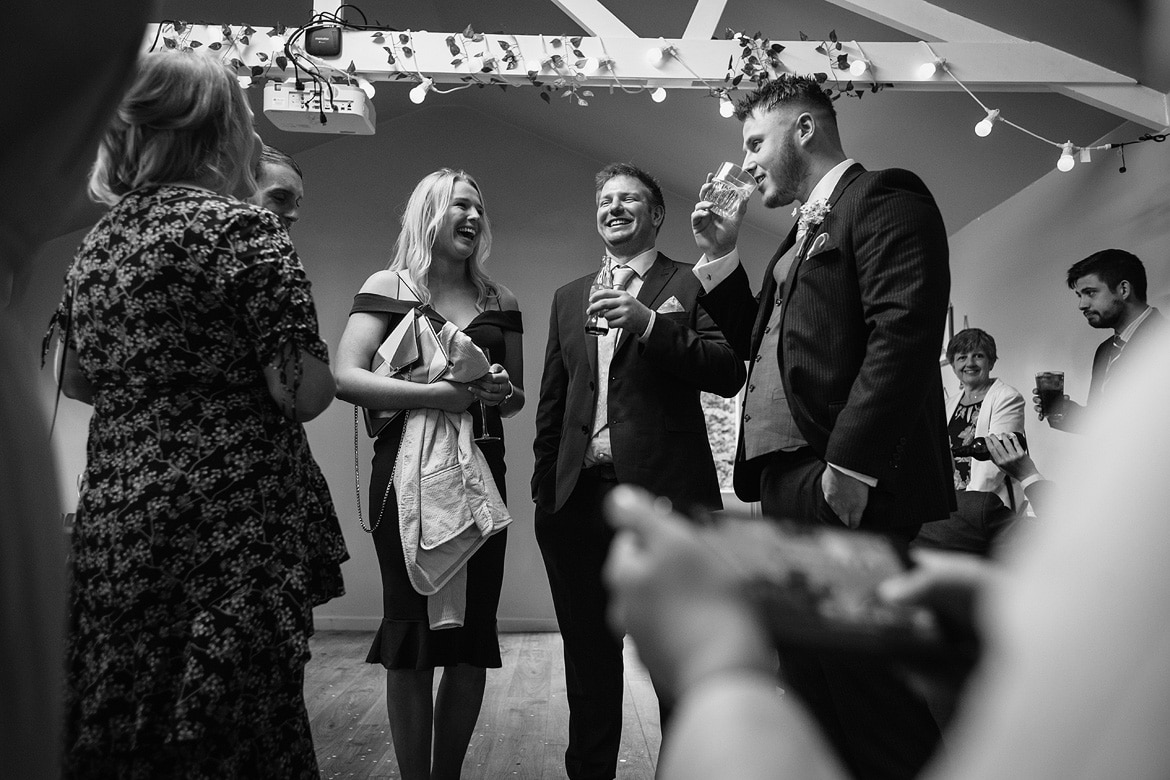 the groom jokes with guests