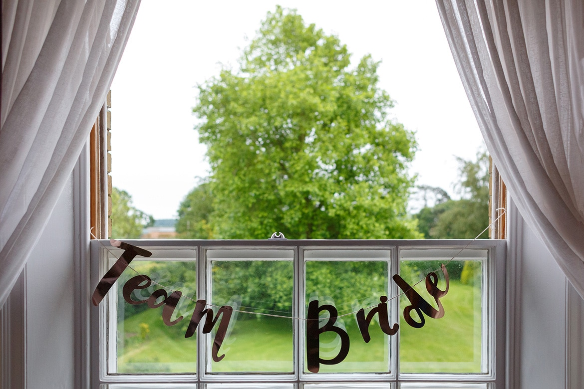 team bride sign hanging in a window at Godwick hall