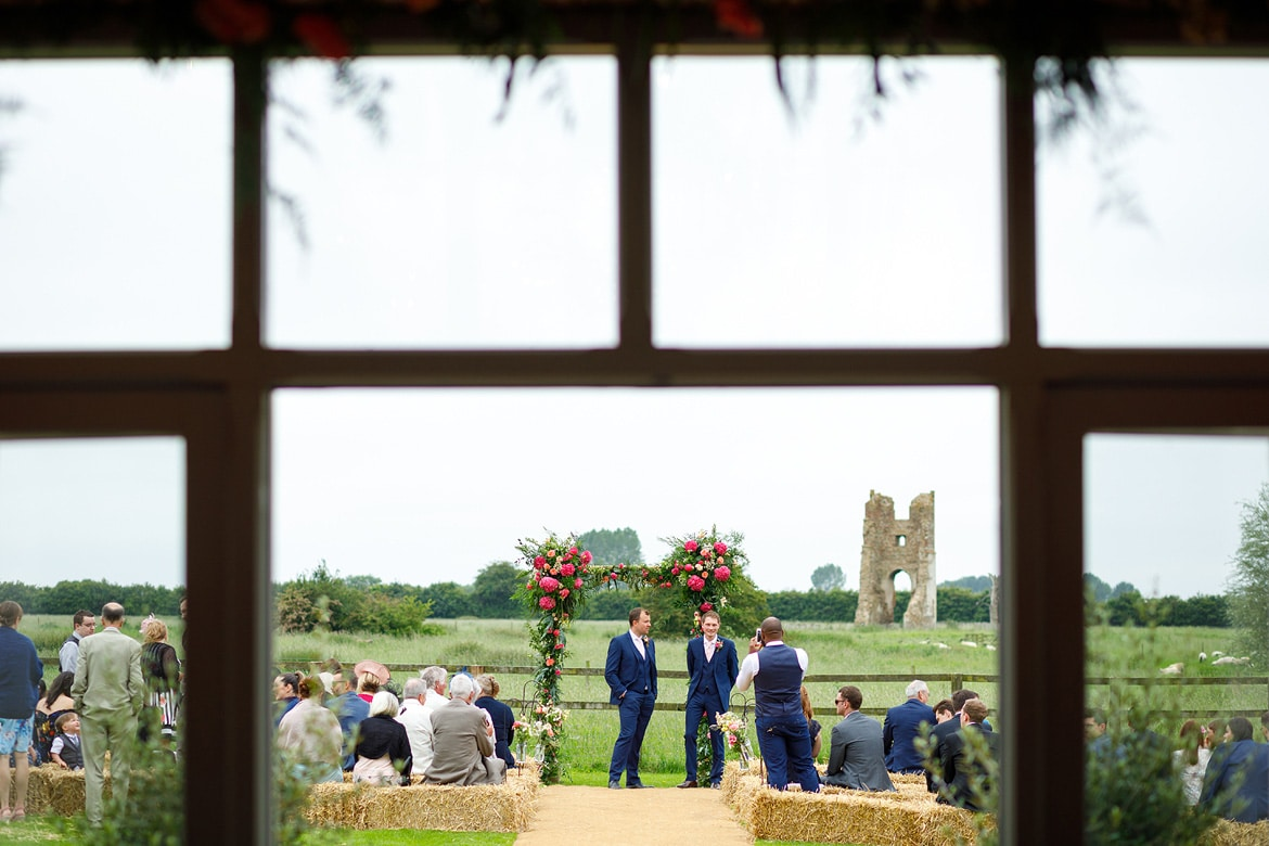 groom and best man wait outside godwick barn