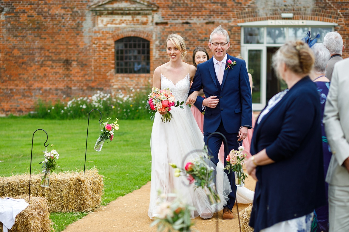laura arrives at her godwick barn wedding ceremony