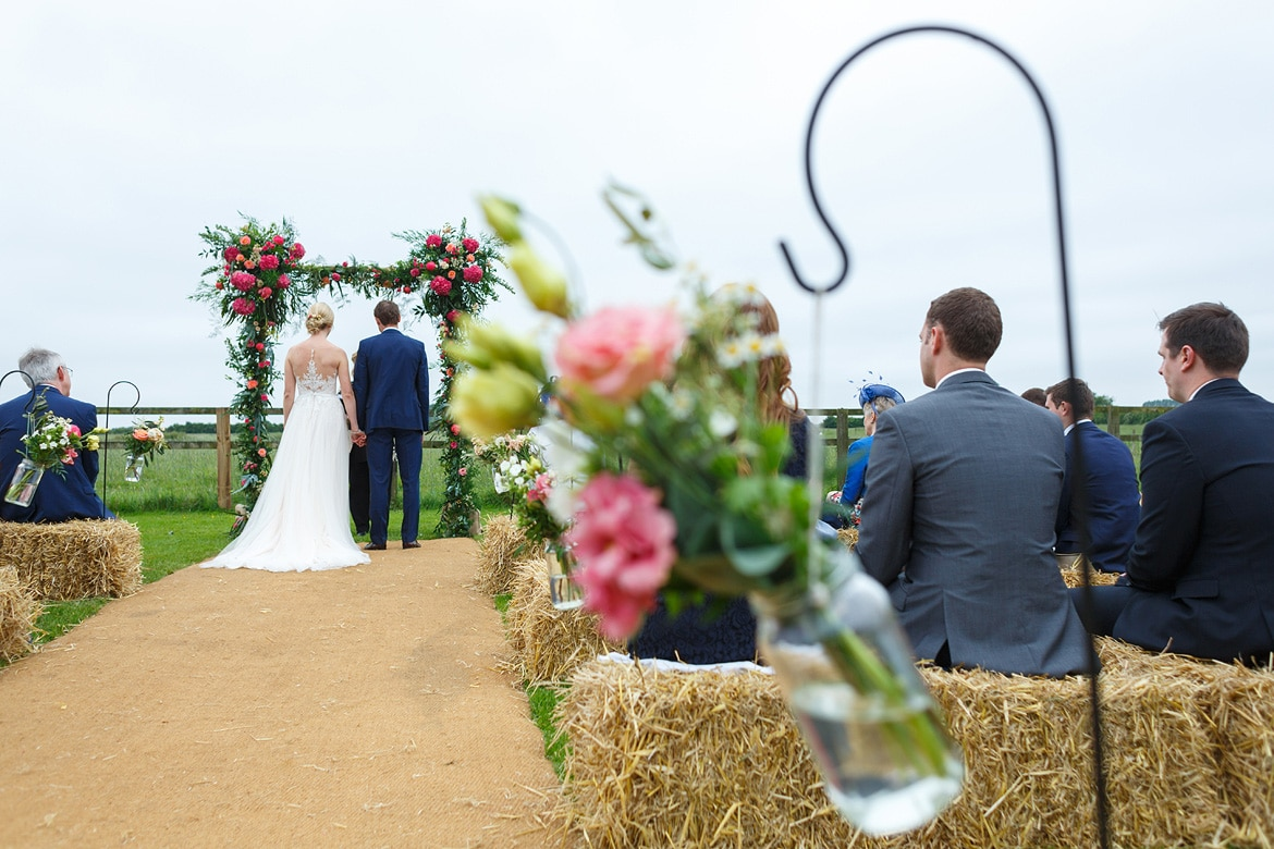 a view from the back of an outdoor wedding ceremony at godwick barn